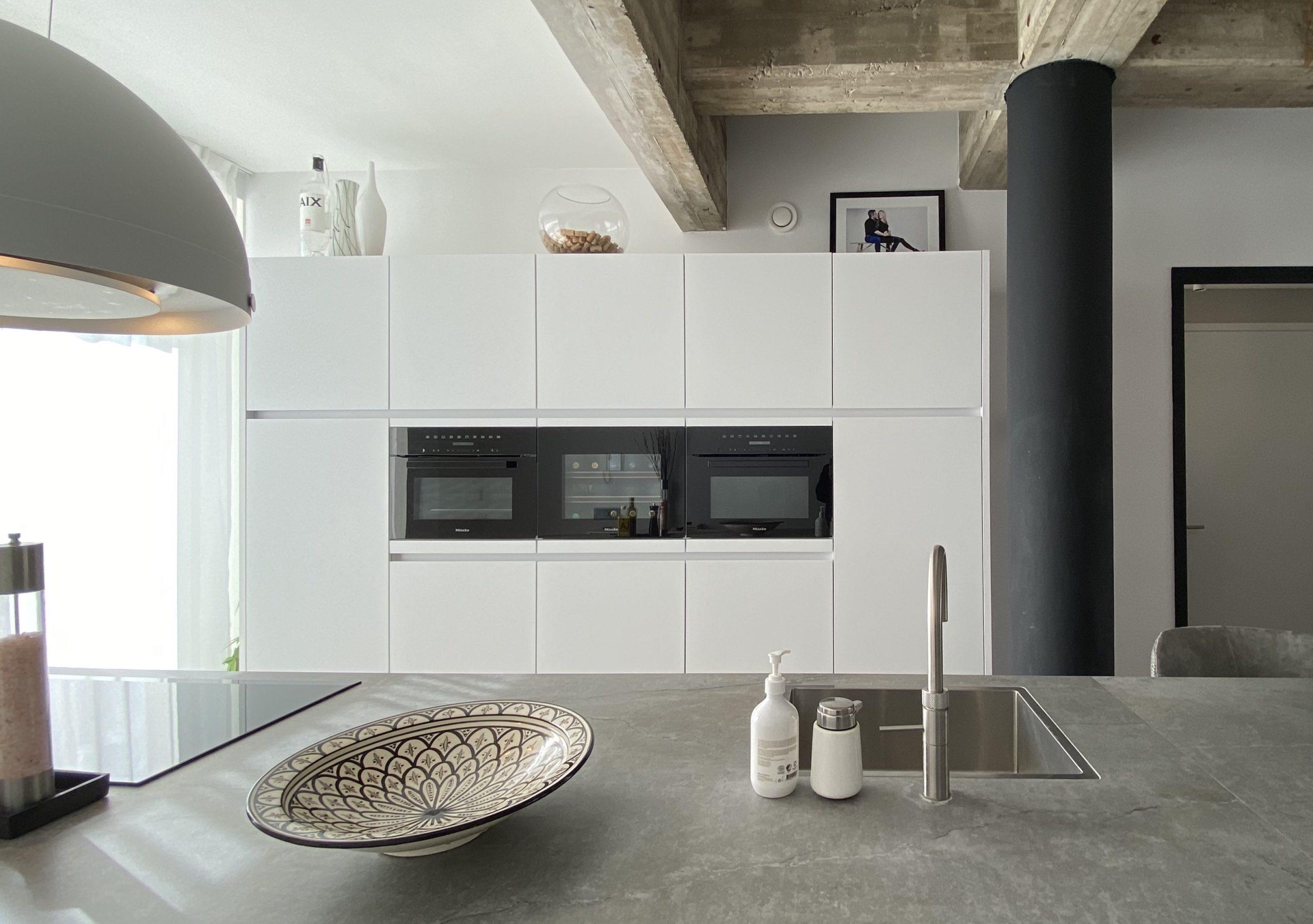 designkeuken met witte kastenwand en miele inbouwapparatuur