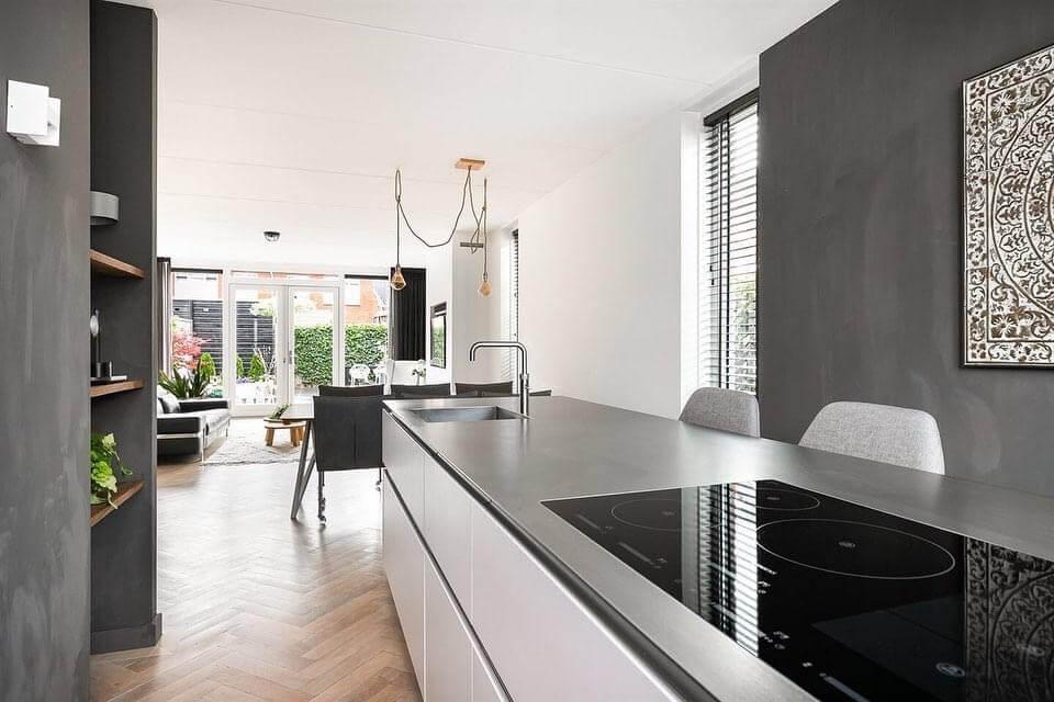 Strakke keuken met kookeiland en ingebouwde kastenwand